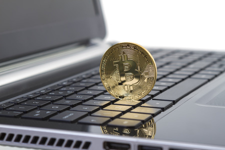crypto: Studio shot of golden Bitcoin virtual currency on laptop. Close-up of front side.