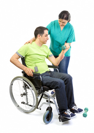 Physical therapist works with patient in lifting hands weights  Young adult in wheelchair
