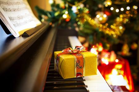 Weihnachtsgeschenk auf Klavier. Weihnachtsschmuck mit Geschenk auf dem Klavier Standard-Bild