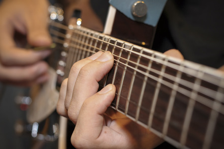 frets: close up shot of a man with his fingers on the frets of a guitar playing
