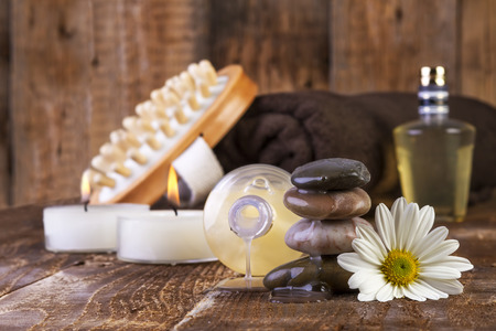 zen basalt stones and spa oil with candles on the wooden background photo