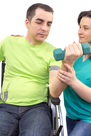 Physical therapist works with patient in lifting hands weights. young adult in wheelchair.