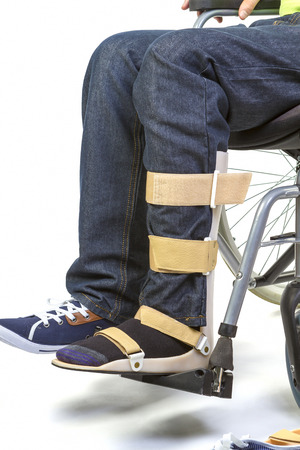 Orthopedist puts orthosis to patient in wheelchair with disabilities photo