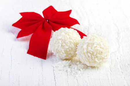 Coconut snowball truffles on white background. Arrangement of coconut cookies on wooden elegant background. photo