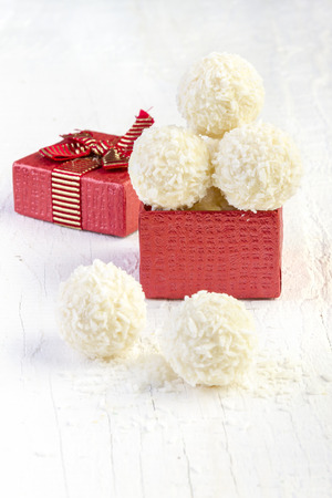 Coconut snowball truffles in the gift box on white background. Arrangement of coconut cookies on wooden elegant background. photo