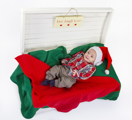 cute baby boy with a santa claus hat in wooden box on white background photo