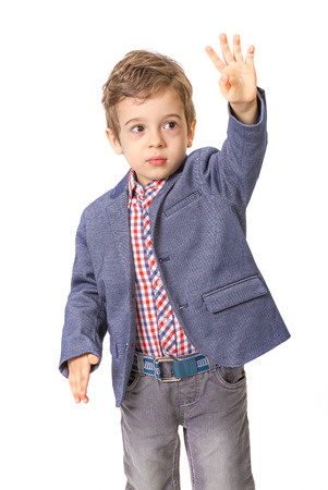 hands lifted up: little boy with jacket and with his hand lifted up on white background Stock Photo