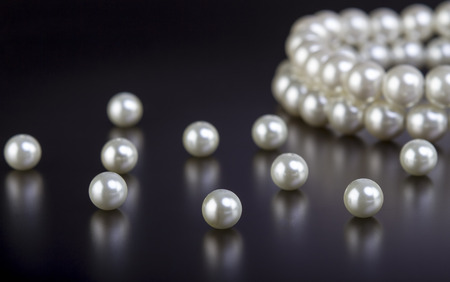 White pearls necklace on black background Foto de archivo