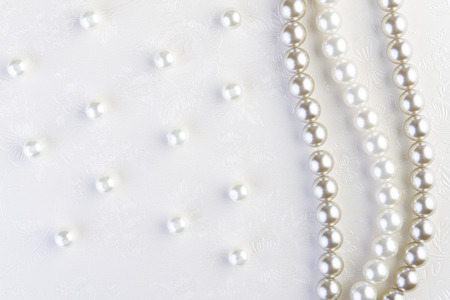 bead jewelry: White pearls necklace on white paper background