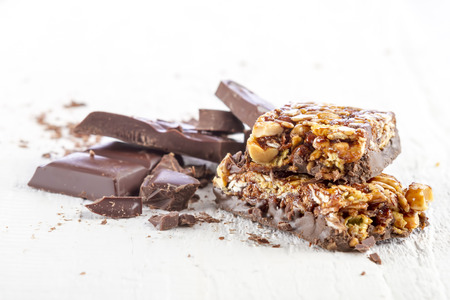 cereal bar: granola bar with chocolate on white wooden background