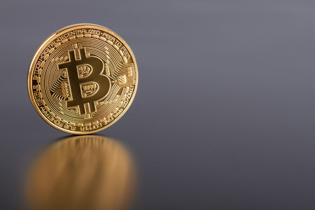 Studio shot of golden Bitcoin virtual currency on gray. Close-up of front side. Stock Photo