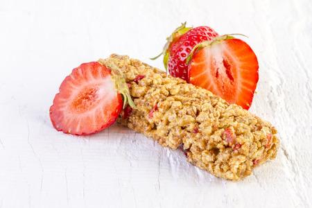 barra de cereal: barritas de muesli con fresas frescas sobre fondo de madera blanca