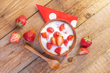 kefir: strawberry and yogurt in a wooden bowl on wooden background
