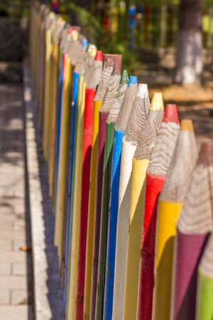 out of context: Fence of colourful pencils outside a preschool. Nice depth of field.