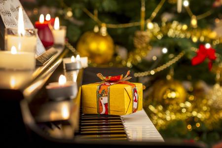 kerze: Weihnachtsgeschenk auf Klavier. Weihnachtsschmuck mit Geschenk auf dem Klavier Lizenzfreie Bilder
