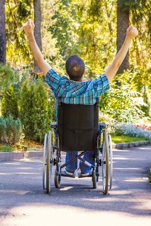 persona alegre: hombre joven en silla de ruedas con los brazos bien abiertos disfrutando de su vida
