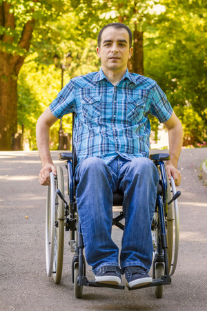 silla de ruedas: hombre joven en silla de ruedas en parque de la ciudad Foto de archivo