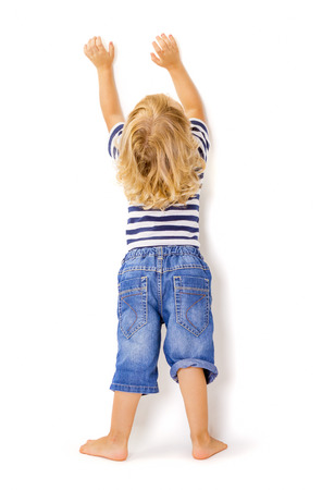 specifies: Back view of little boy with hands up on white background