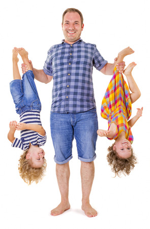 a young baby: Happy father holding his smiling children upside down isolated on white background.