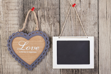 love shape: Empty wooden blackboard sign and heart shape frame with love text on wooden background. Stock Photo