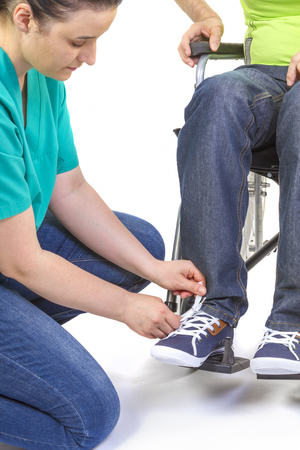 get dressed: Nurse helping a disabled young man in wheelchair get dressed. Stock Photo