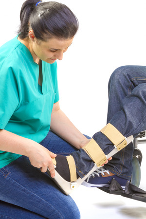 foot doctor: Orthopedist puts orthosis to patient in wheelchair with disabilities