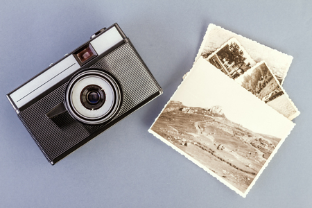 Vintage photo camera and old photos on a gray table