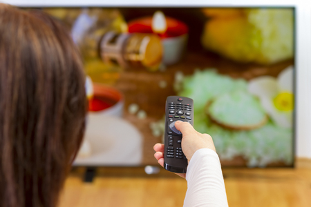 watch video: Over the shoulder view of girl sitting on sofa holding tv remote and surfing programs on television. Focus on the remote control.