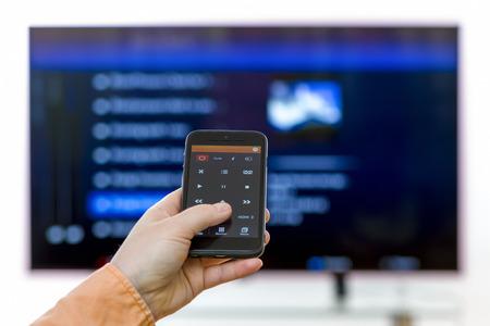 Primer en la mano de la mujer que sostiene smartphone y utilizar una aplicación con programas de control y de surf a distancia de la televisión. Centrarse en el control remoto.