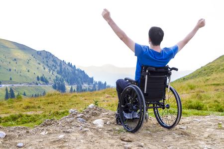 산에 화창한 날에 신선한 공기를 즐기는 휠체어에 젊은 남자