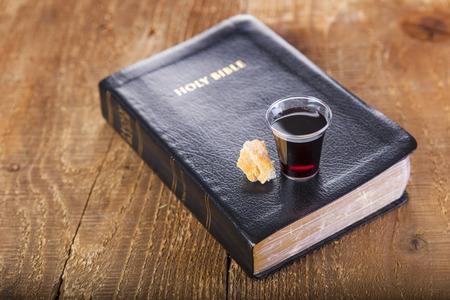 Przyjmowanie komunii. Filiżanka szkło z czerwonym winem, chlebem i Świętą biblią na drewnianym stołowym zakończeniu ,. Skup się na szkle