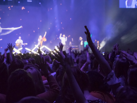 Audience with hands raised at a music festival and lights streaming down from above the stage. Focus on hands Editorial