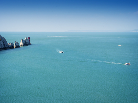 extremity: The Needles - is a row of three distinctive stacks of chalk that rise out of the sea off the western extremity of the Isle of Wight, UK, close to Alum Bay.  Stock Photo