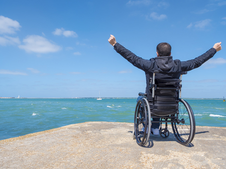 Disabled alone young man sitting in a wheelchair and looks at the sea.