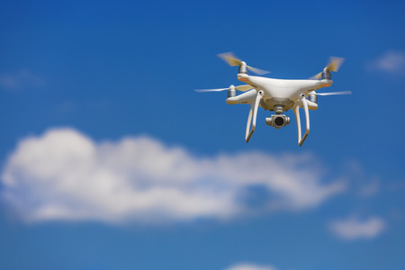 Professional camera drone flying in clear blue sky partly clouded Stockfoto
