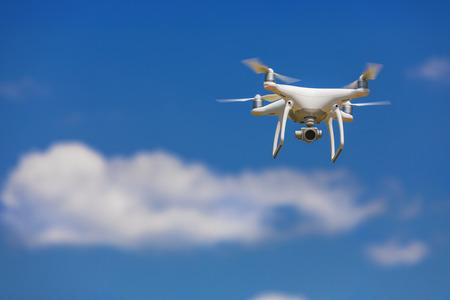Professionele camerahommel die in duidelijke blauwe gedeeltelijk bewolkte hemel vliegen