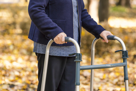 Closeup of senior woman legs walking with walker in autumn park.