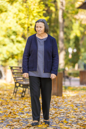 Depressed senior woman thinking worried outdoors in park.