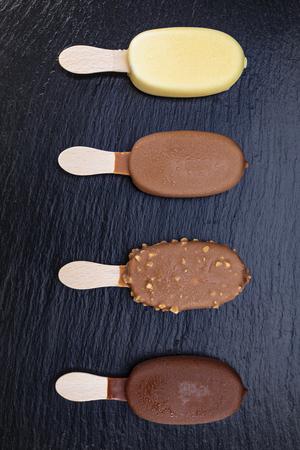 Ice cream on stick covered with chocolate on black stone slate board. Standard-Bild