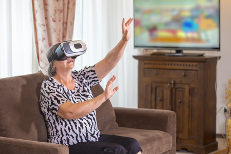 Senior woman with virtual headset or 3d glasses playing videogame at home. Technology, augmented reality, entertainment and people concept. Focus on her hands!