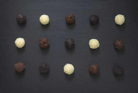 Fancy dark milk white chocolate truffles ready to eat on black stone background.