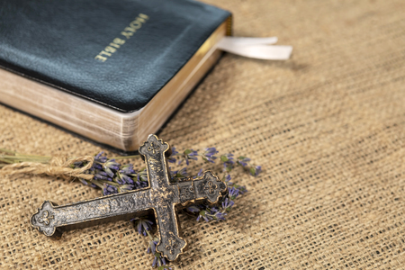 Closeup of metalic Christian cross on lavanda flowers next to Holy Bible on textile background.