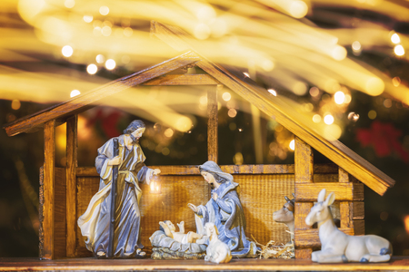 Christmas Manger scene with figurines including Jesus, Mary, Joseph and sheep. Focus on mother! Lights trail in front of camera. Zdjęcie Seryjne