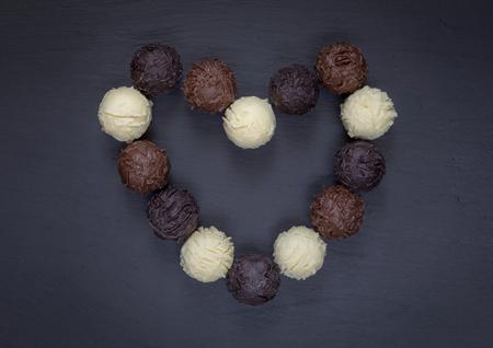 Chocolate truffles assortment heart shape on black stone. Zdjęcie Seryjne