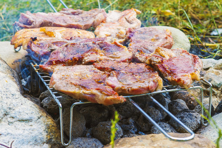 Outdoor grilling pork meat on charcoal grill fire