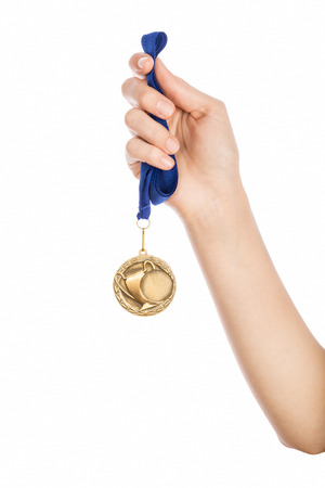 Girl hand raised holding gold medal against white background award and victory concept Zdjęcie Seryjne