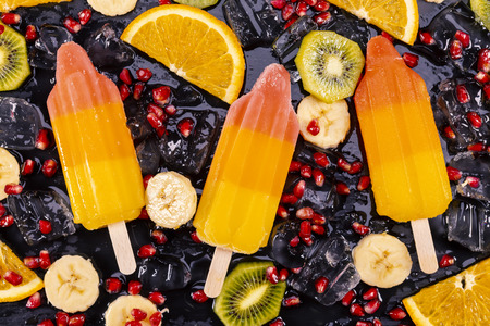 Fruit ice cream on stick with slices fruits on black slate board.