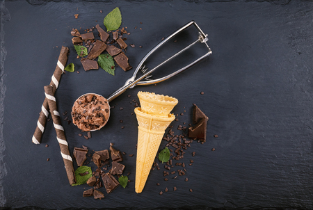 Chocolate ice cream in scoop with wafer sticks, cone and chocolate on a black slate board. Focus on ice cream in scoop. Zdjęcie Seryjne