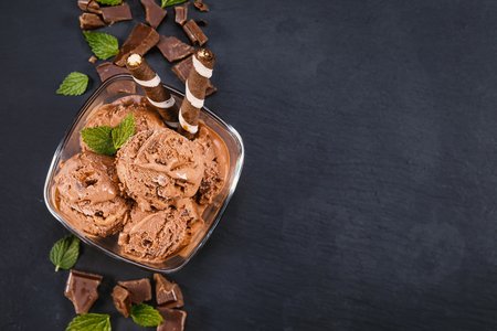 Scoops chocolate ice cream in glass bowl with wafer sticks, cone and chocolate on a black slate board. Focus on Bowl with scoops chocolate ice cream