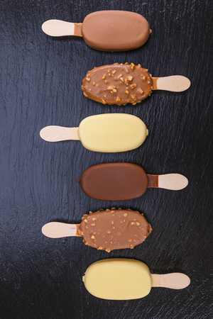 Ice cream on stick covered with chocolate on black stone slate board. Zdjęcie Seryjne